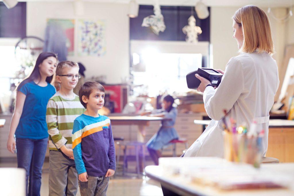 Augenscreening Bild über die Krankenschwester mit Kinden in der Schule